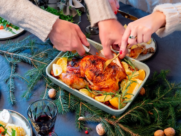 家族は食べ物の完全なクリスマステーブルに座っています。