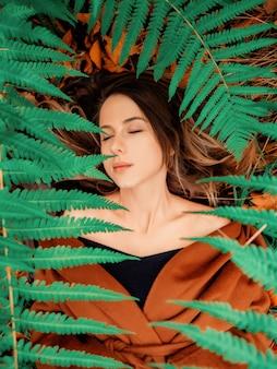 Женщина лежит на земле в лесу, вокруг папоротников
