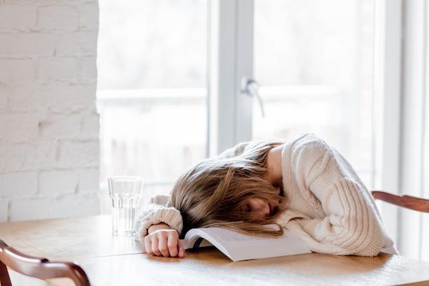 Усталая девушка в белом свитере с книгой на кухне