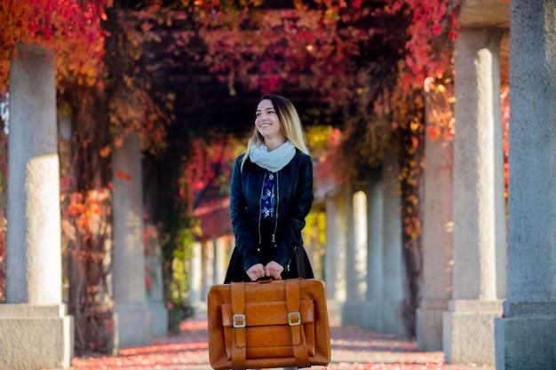 Молодая девушка с чемоданом в аллее красного винограда