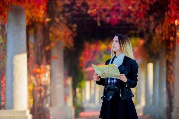 Молодая девушка с картой и камерой пытается найти способ