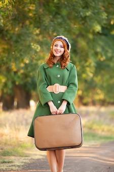 木の路地でスーツケースを持った赤毛の女の子。