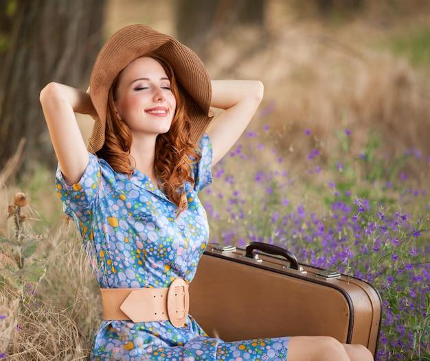 秋の草に座っているスーツケースで赤毛の女の子