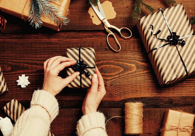テーブルにクリスマスプレゼントをラッピングする女性