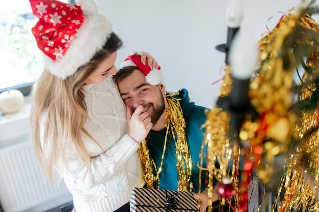 クリスマス帽子の若いカップルがクリスマスと新年の家を飾る