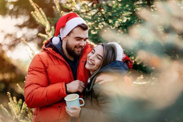 モミの木の近くのクリスマス帽子でロマンチックなカップル。