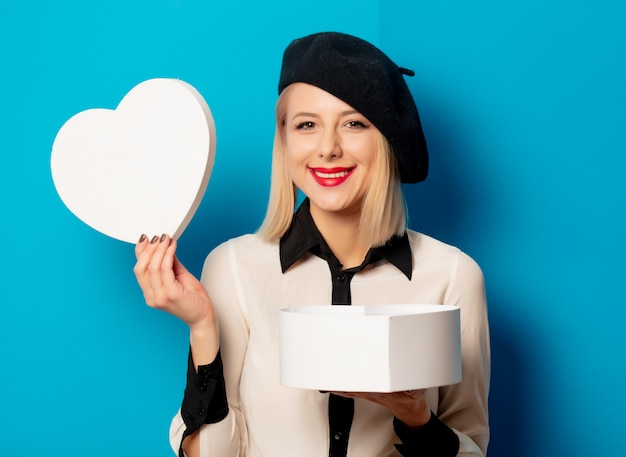 ベレー帽の美しいフランス人女性は、青い壁にハート型の箱を保持しています