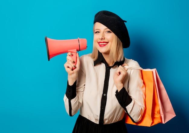 Красивая французская женщина в берете с сумками и громкоговорителем
