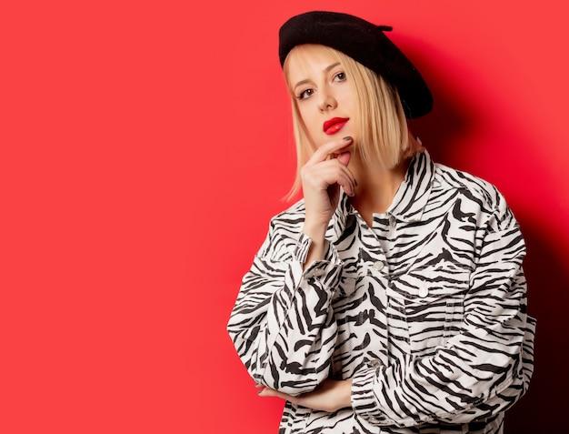 Красивая женщина в берете и куртке с принтом зебры на красной стене