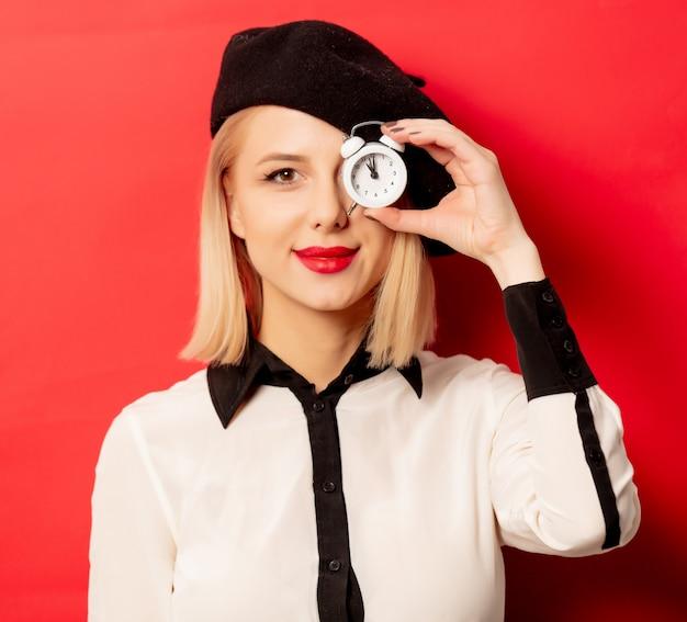 Красивая французская женщина в берете с будильником на красной стене