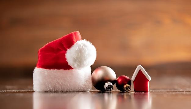 サンタクロースの帽子と木製のテーブルの小さな家