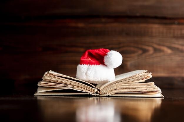 古い本と木製のテーブルのクリスマス帽子