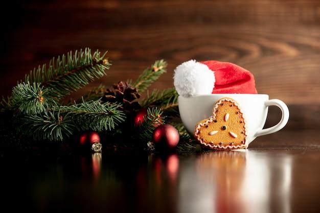 サンタクロースの帽子とカップとジンジャーブレッドのクッキー