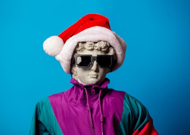Античная статуя, одетая в модную одежду девяностых и шляпу санта-клауса