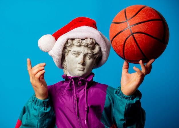 Античная статуя, одетая в модную одежду девяностых и шапка санта-клауса, держит баскетбольный мяч
