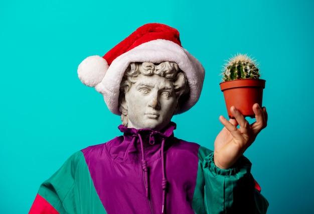 Античная статуя, одетая в модную одежду девяностых и в шапке санта-клауса, держит кактус