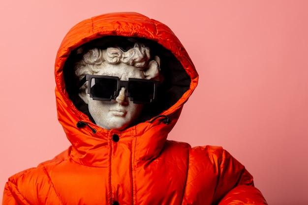 ダウンジャケットとサングラスに身を包んだアンティークの像