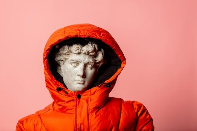 Античная статуя, одетая в пуховик на розовой стене