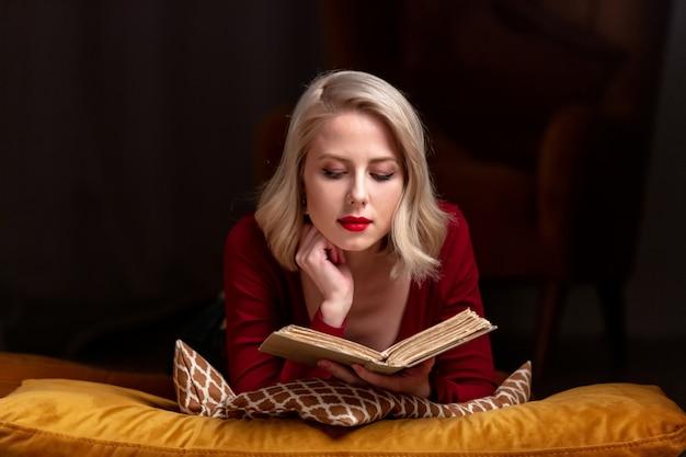 Красивая белокурая женщина с книгой лежит на подушках