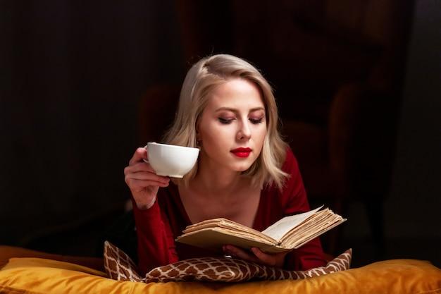 Красивая белокурая женщина с книгой и чашкой лежит на подушках
