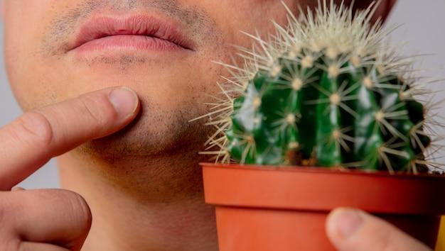 Мужчина держит кактус возле лица