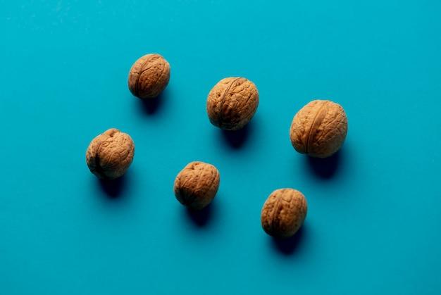 Четыре грецких ореха на синей поверхности