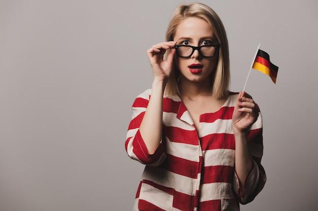 Красивая девушка в очках держит немецкий флаг