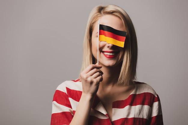 Красивая девушка держит немецкий флаг