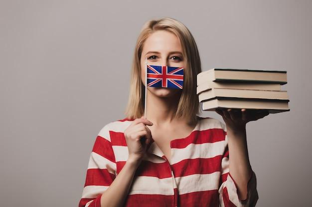 美しい少女は英国の旗と本を保持しています。
