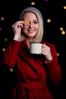 一杯のコーヒーとジンジャーブレッドのクッキーを持つ少女