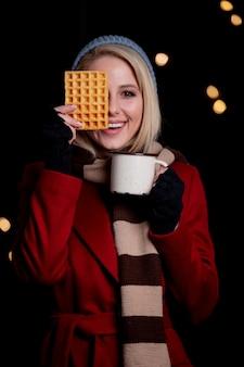 一杯のコーヒーとワッフルのブロンドの女の子