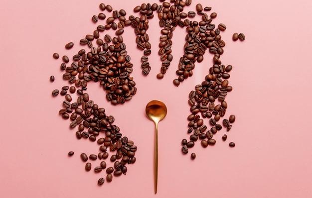 ティースプーンとピンクの壁に人間の手の形のコーヒー