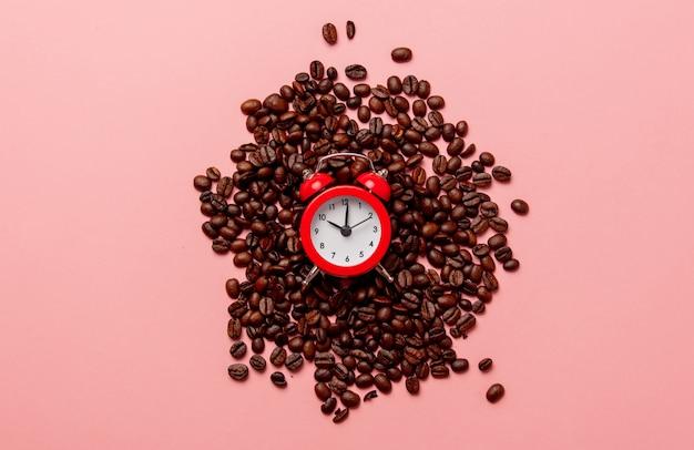 Красный маленький будильник и кофейные зерна