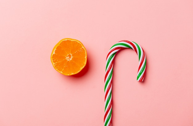 Рождественские конфеты и апельсин на розовой стене