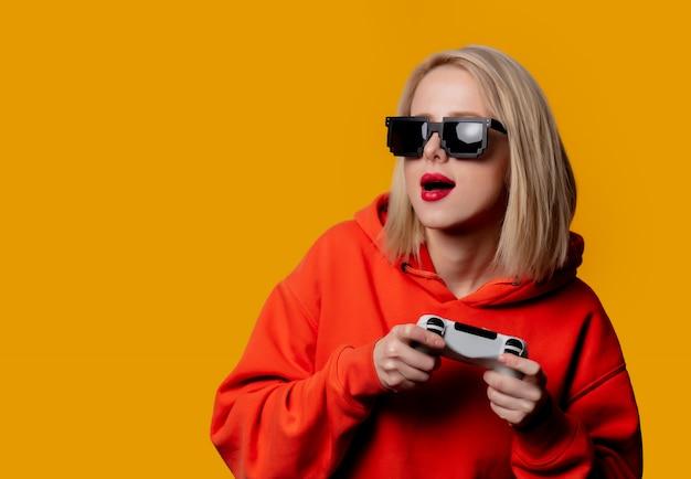 Девушка в солнечных очках играет с джойстиком