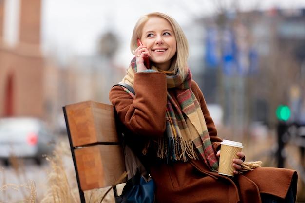 一杯のコーヒーと携帯電話で美しい金髪の女性