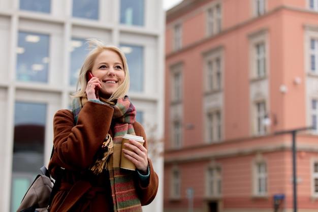 携帯電話で話しているコーヒーのカップを持つ女性
