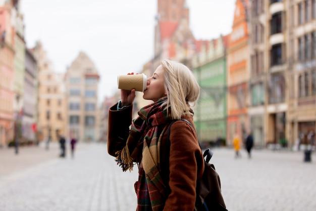 美しい金髪の女性は、旧市街でコーヒーを飲む