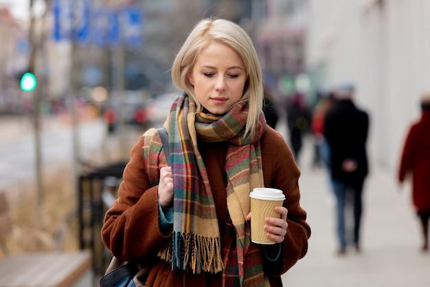 街でコーヒーのカップを持つ美しい金髪の女性