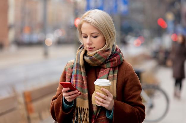 携帯電話を使用してコーヒーのカップを持つ美しい金髪の女性