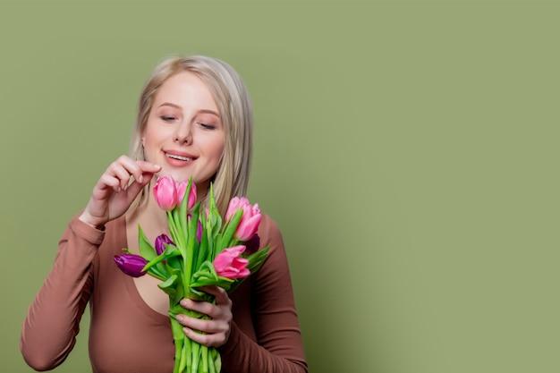 Красивая блондинка в коричневой блузке с тюльпанами