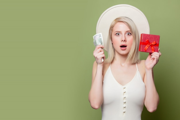 Красивая белокурая девушка с деньгами и подарочной коробкой
