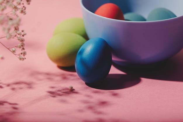 Пасхальные яйца, цветок и тарелка на розовом фоне