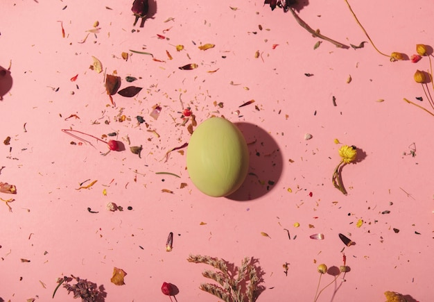 ピンクの背景の乾燥した植物の装飾と黄色の卵