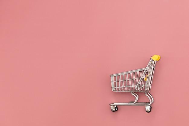 ピンクの背景の金属のショッピングカート。