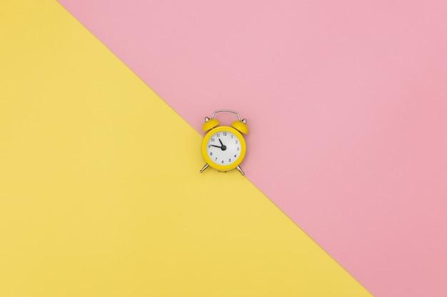 ピンクと黄色の背景に黄色の小さな目覚まし時計