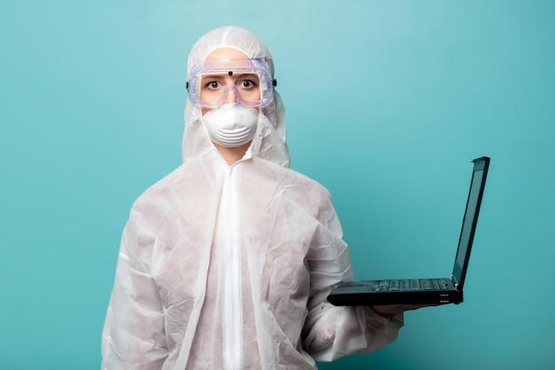 ラップトップコンピューターでウイルスに対する防護服を着ているメディック女性