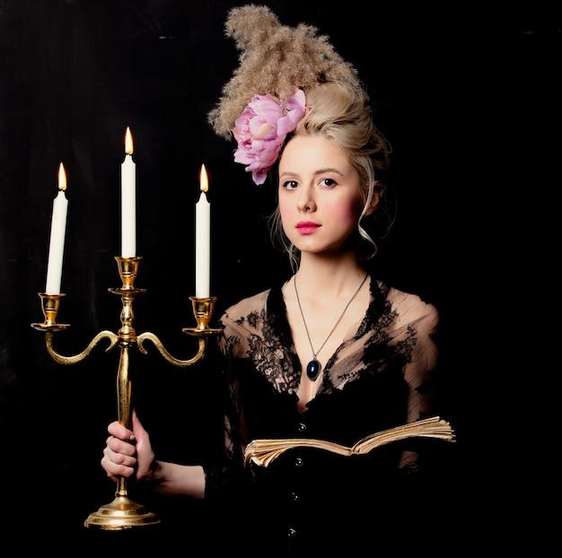 Красивая блондинка графиня с книгой и подсвечником