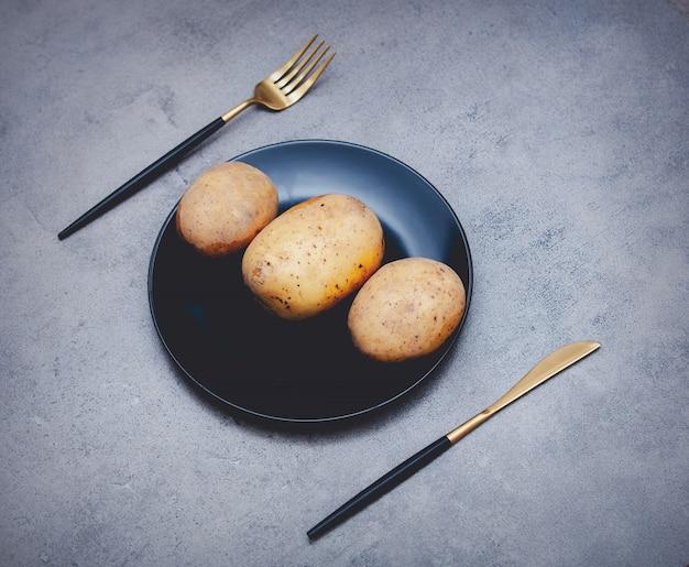 ナイフとフォークで皿にジャガイモ