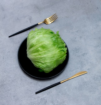 フォークとナイフで皿にレタス。